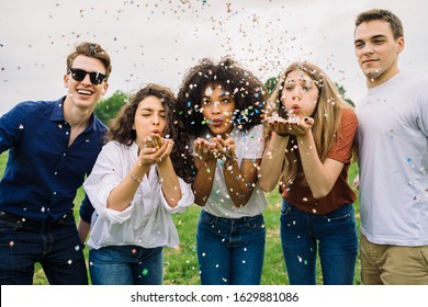 Group of four friends having fun at the park blowing confetti - Millennials playing together at sunset