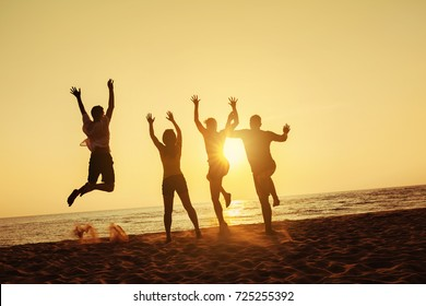 Group of four friends having fun, run and jump on sunset beach. Sea trave holidays concept. Space for text