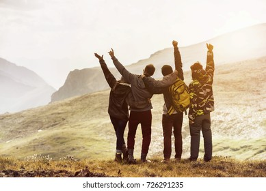 Group of four friends having fun and raising arms at mountain top. Space for text