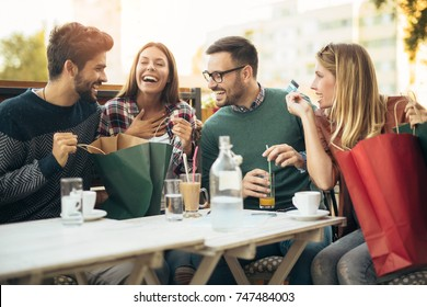 Group of four friends having fun a coffee together after shopping