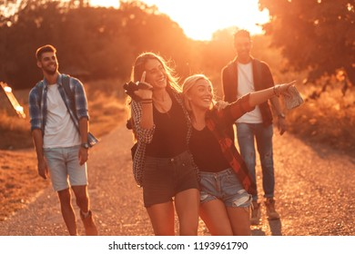 Group of four friends hiking through countryside together at sunset.