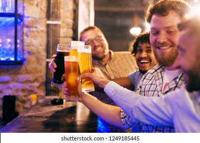 Group of four friends making a toast while standing at bar. Pub interior.