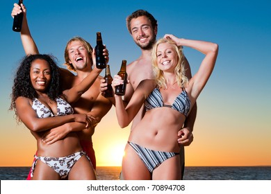 Group of four friends - men and women - standing with drinks on the beach against the setting sun over the ocean