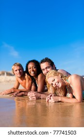 Group of Four friends - men and women - on the beach having lots of fun in their vacation