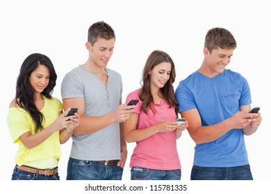 A group of four friends standing slightly to the side as they all send texts on their phones