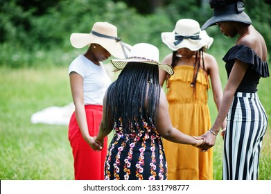 Group of four gorgeous african american womans wear summer hat holding hands and praying at green grass in park.