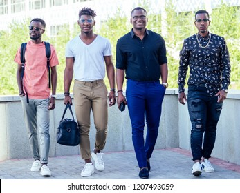 a group of four handsome African businessman American man stylish walk in the park