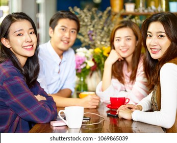 group of four happy asian young adults man and woman looking at camera smiling while gathering in coffee shop.