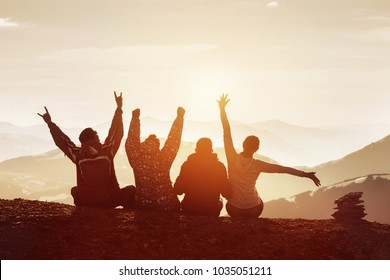 Group of four happy friends is having fun with raised hands against sunset mountains
