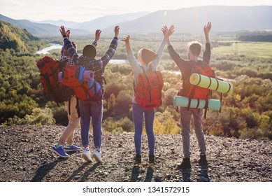 Group of four happy friends jumps at the sunset on mountains background. Traveling, tourism and friendship concept. View from back.