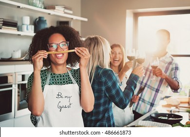 Group of four happy friends playing with food while preparing a meal or dinner or a culinary class indoors