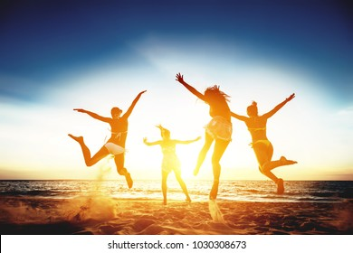 Group of four happy girls runs and jumps against sunset sea beach. Tropical vacations concept