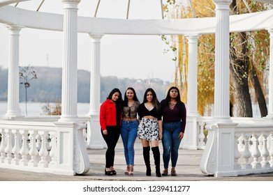 Group of four happy and pretty latino girls from Ecuador posed at street against ancient arch.
