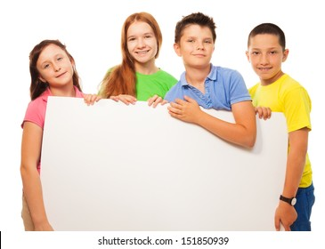 Group of four happy smiling friends, two girls and couple boys, holding blank white sign advertising close portrait