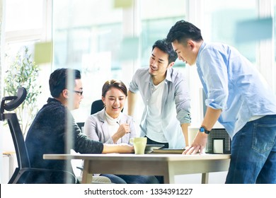 group of four happy young asian corporate executives working together meeting in office discussing business in office.