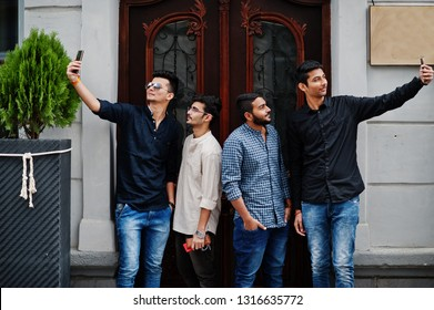Group of four indian ethnicity friendship togetherness mans. Technology and leisure, guys with phones. Making selfie.