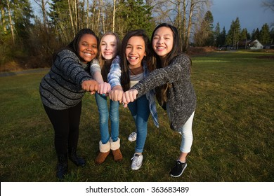 Group of four kids making a unified fist to demonstrate girl pow