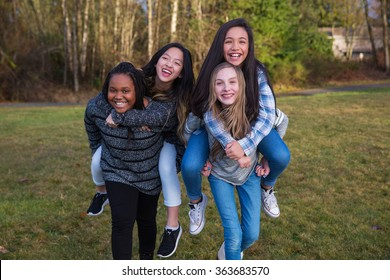 Group of four kids playing and giving piggyback rides