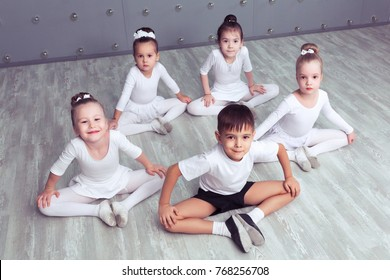 Group of four little ballerinas and kid ballerun posing together and practicing for their first performance in different dance poses