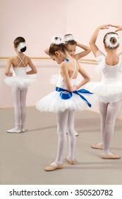 Group of four little ballerinas posing together and practicing for performance. One of them fixes the tape with a bow around her waist. They are good friend and amazing dance performers