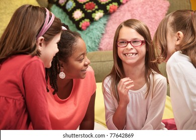 Group of four little girls laugh at a sleepover