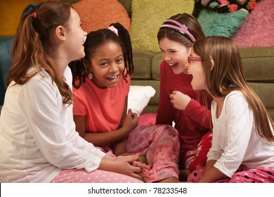Group of four little girls in pajamas laugh at a sleepover