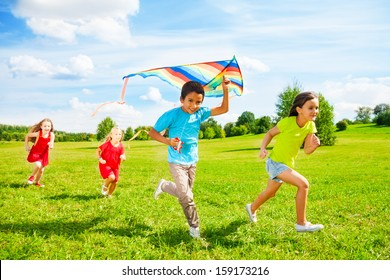 Group of four little kids, boy and girls running with kite in the park on summer day