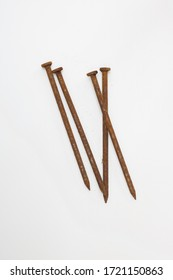 Group of four long rusty nails against plain white background