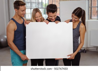 Group of four male and female young adult athletes holding large blank white poster together at small fitness gymnasium