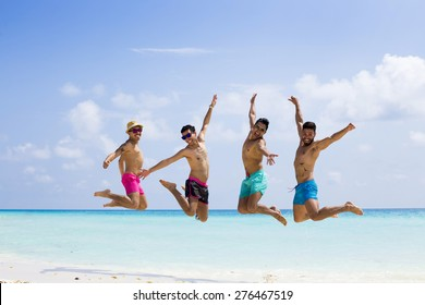 Group of four men jumping at the beach