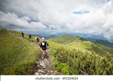 group of four men running on high mountain ridge trail with beautiful view and sky clouds