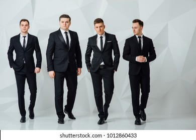 Group of four men in suits white background