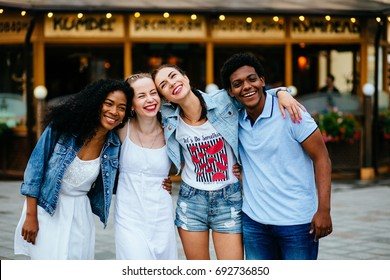 Group of four multiethnic hipster teenager friends hugging and laughing over shopfront of cafe or pub in summer time. Multiethnic friendship and people concept.