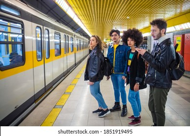 Group of four multiethnic people tourist commuter in the underground waiting for subway using smartphone