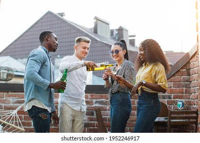 Group of four multiracial friends in stylish casual clothes drinking alcohol, smiling and chatting on roof top. Young people hanging out together during weekends.