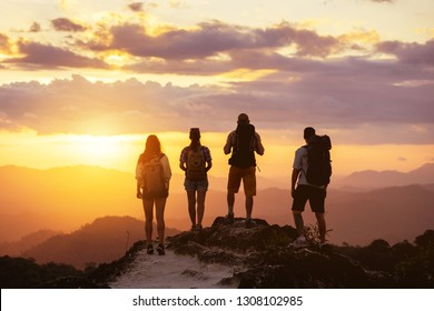 Group of four peope's silhouettes stands on mountain top and looks at sunset