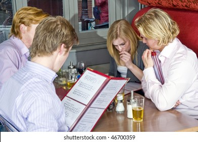 a group of four people choosing dishes from the menu in a restaurant