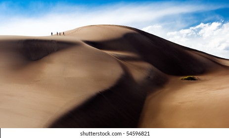A group of four people climb to the top of the dune field of the Great Sand Dunes National Park in Colorado