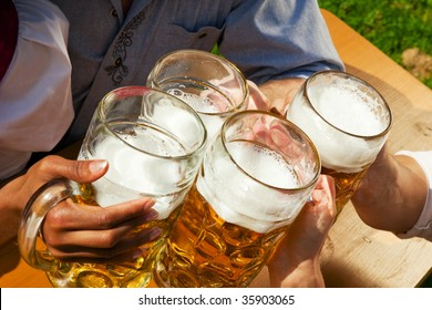 Group of four people in Couple in traditional Bavarian dress, Lederhosen and Dirndl, in a beer garden or at a festival like the Oktoberfest; focus on beer steins