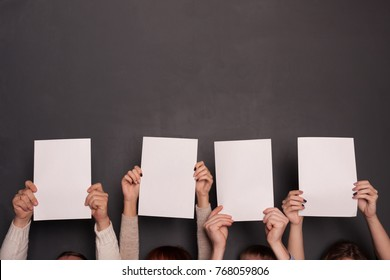 Group of four people holding paper sheets above heads on gray background. Mockup template for team work in business concept