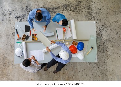 Group of four people including engineer and businessmen discuss and review about construction material, taken from bird eyes view, top angle