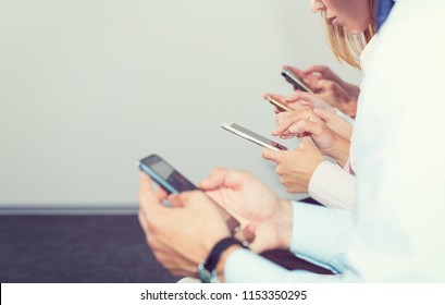 Group four people look in mobile phones. Office staff addiction to new technology trends. Concept business people using smartphone on social network. Follow news and exchange rates, trading. Internet.
