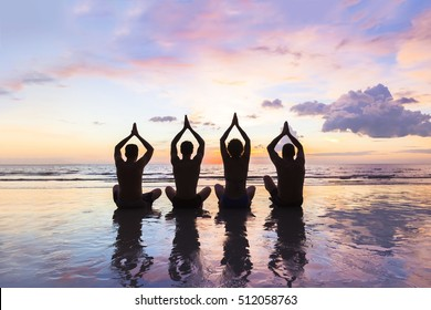 Group of four people practicing meditation and yoga on the beach at sunset - concept about friends, family, harmony and healthy lifestyle