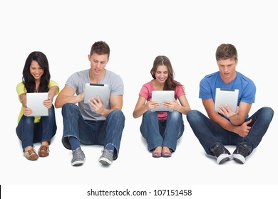 A group of four people sitting beside each other on the ground as they all use their tablet pc's