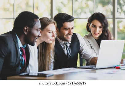 Group of four professional African and Caucasian businessmen and businesswomen gathered in front of laptop with smiling to talking and planning their new trend project at the office working table