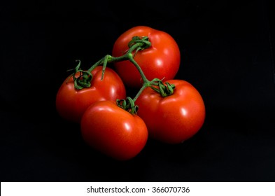 Group of four red tomatoes with black background