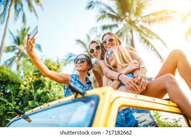 group of four russian female tourist friends taking selfie on top of offroad truck at koh samui thailand with smart phone