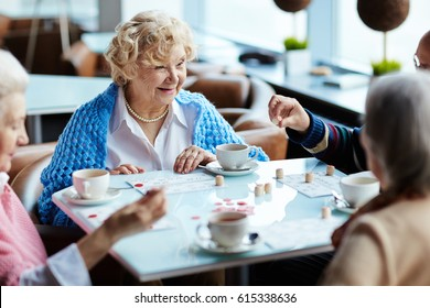 Group of four senior people gathered together in small cozy cafe, drinking fragrant tea and playing lotto with interest
