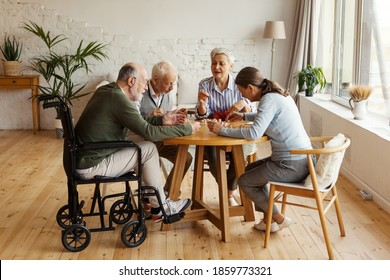 Group of four senior people, two men including disabled one and two women, sitting at table together and playing bingo game in nursing home