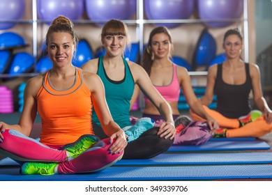 group of four smiling women sitting in lotus pose on mat at gym